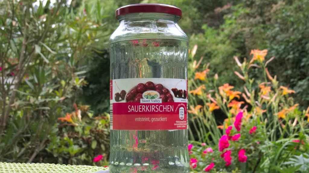Einwegglas für Sauerkirschen, in dem sich nun Zuckerwasser befindet.