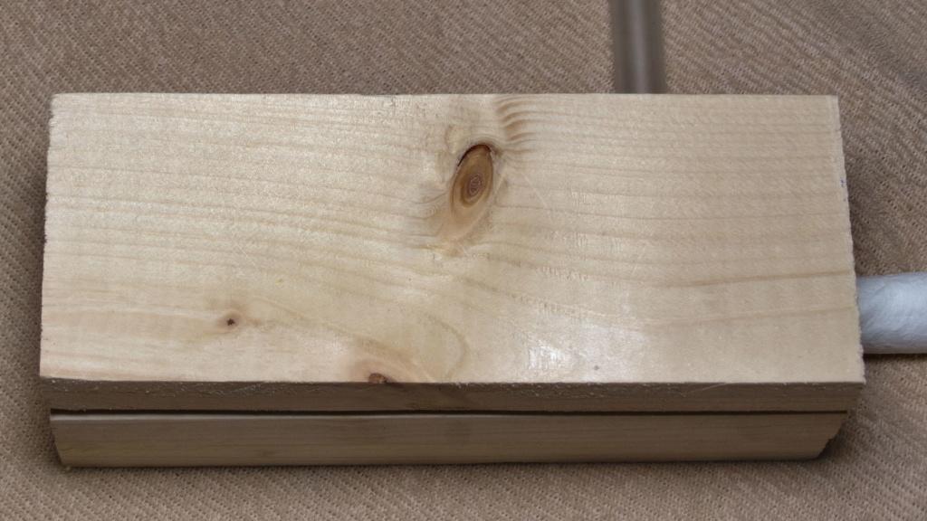 Man sieht ein Holznest, das mit einem Stück Holz abgedeckt ist